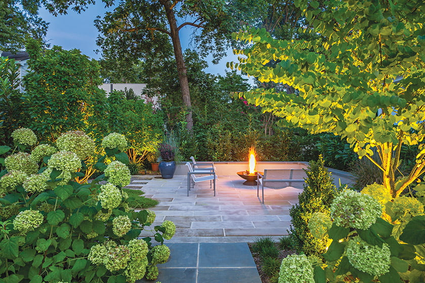 Cutting Edge— In this reimagined garden in Arlington, a cast-iron fire pit animates the flagstone terrace.