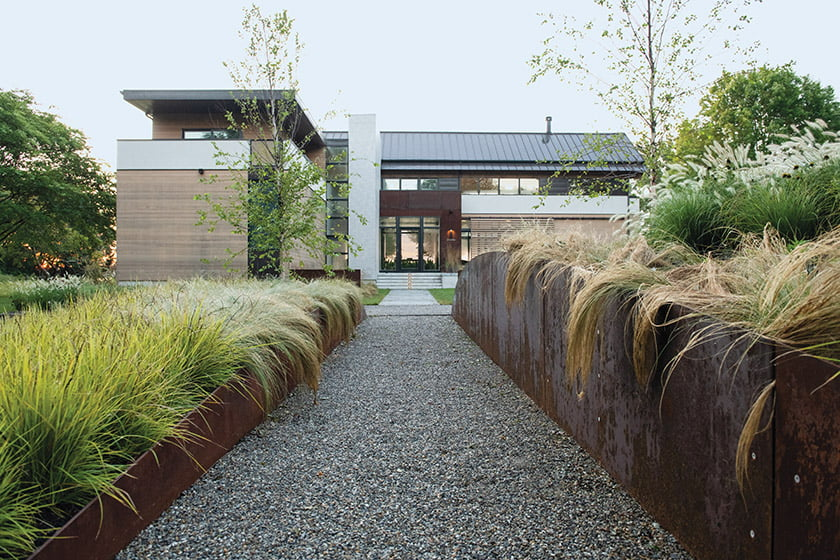 Cedar siding, a gabled aluminum roof and weathered Corten steel panels detail the home. An axis leads guests through the arrival garden and into the foyer. Photo: Mason Summers