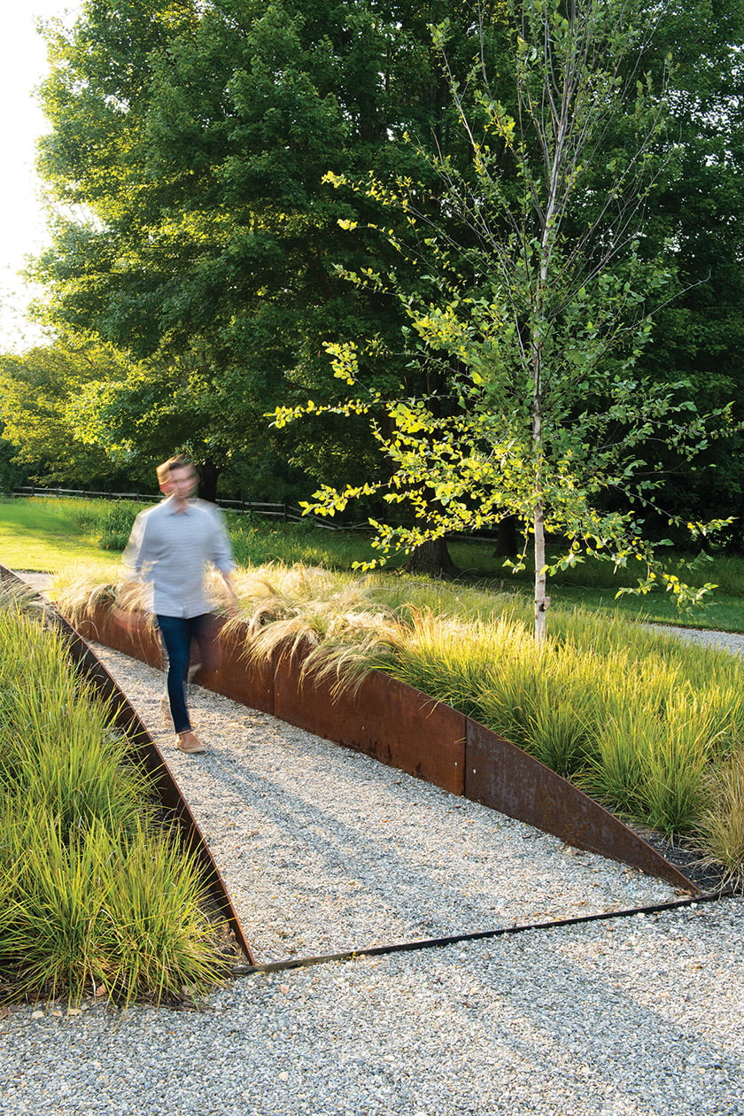 Corten steel panels carve a path, on axis with the home's entryway, through an elliptical garden mound lush with native grasses and perennials. Photo: Mason Summers