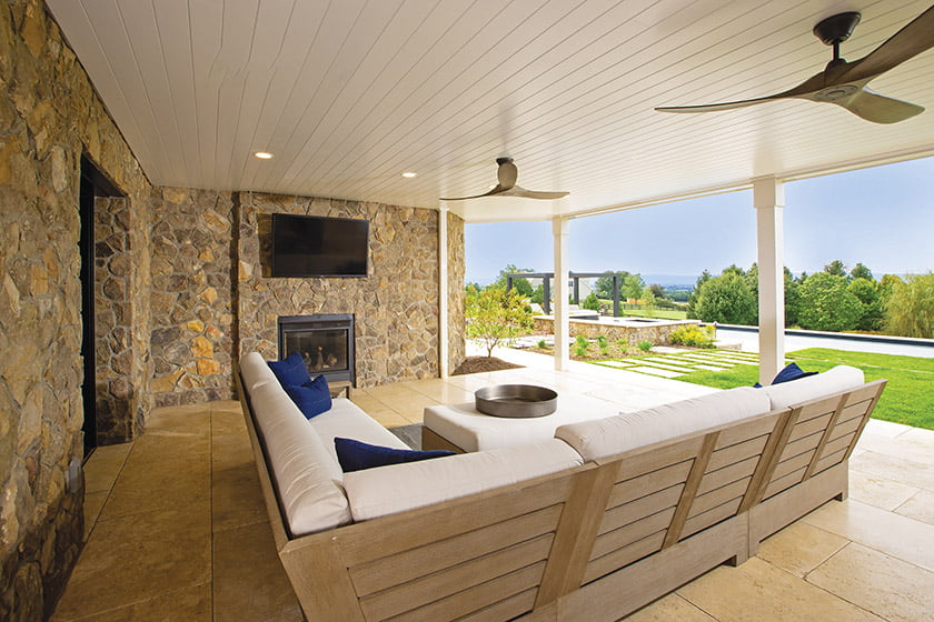 The finished lower level opens to a covered porch bordered by stone foundation walls.