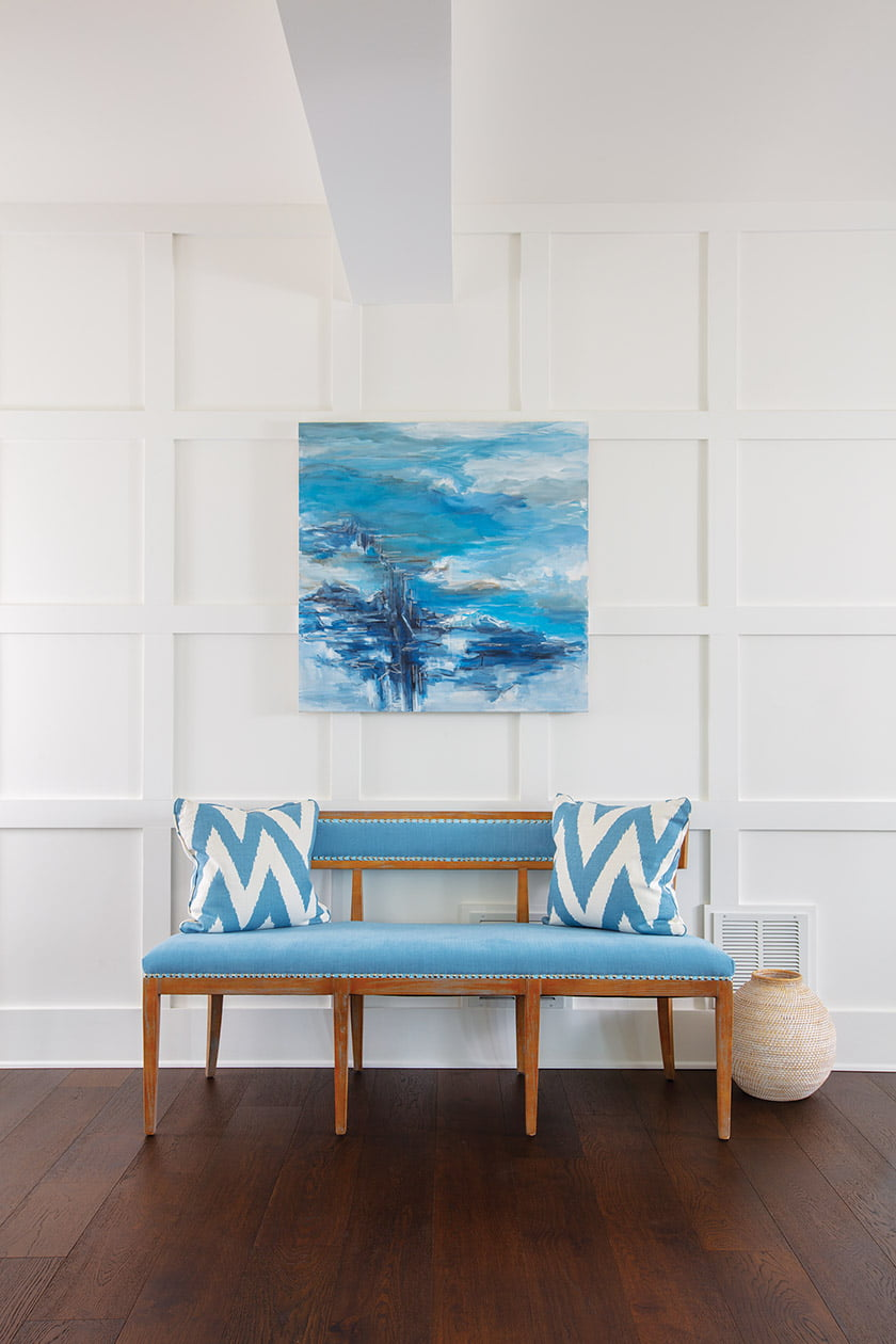 A bench in the entry hall pairs with art by Suzanne Yurdin.