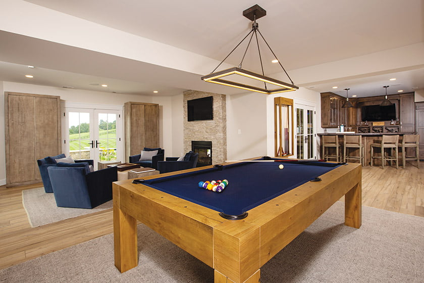 Rustic wood accents and built-in storage embellish the interior spaces, which include areas for billiards and watching TV.