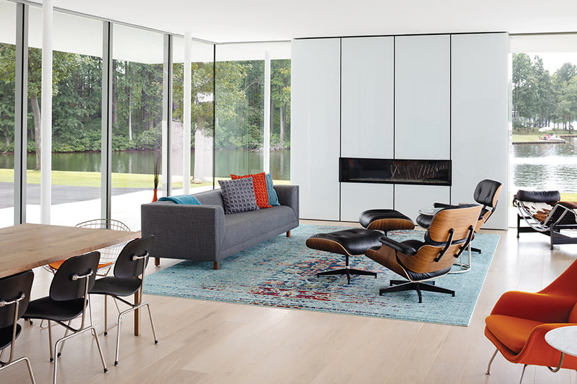 The great room is furnished with a Safavieh rug, Herman Miller sofa and Eames lounge chairs and ottomans.
