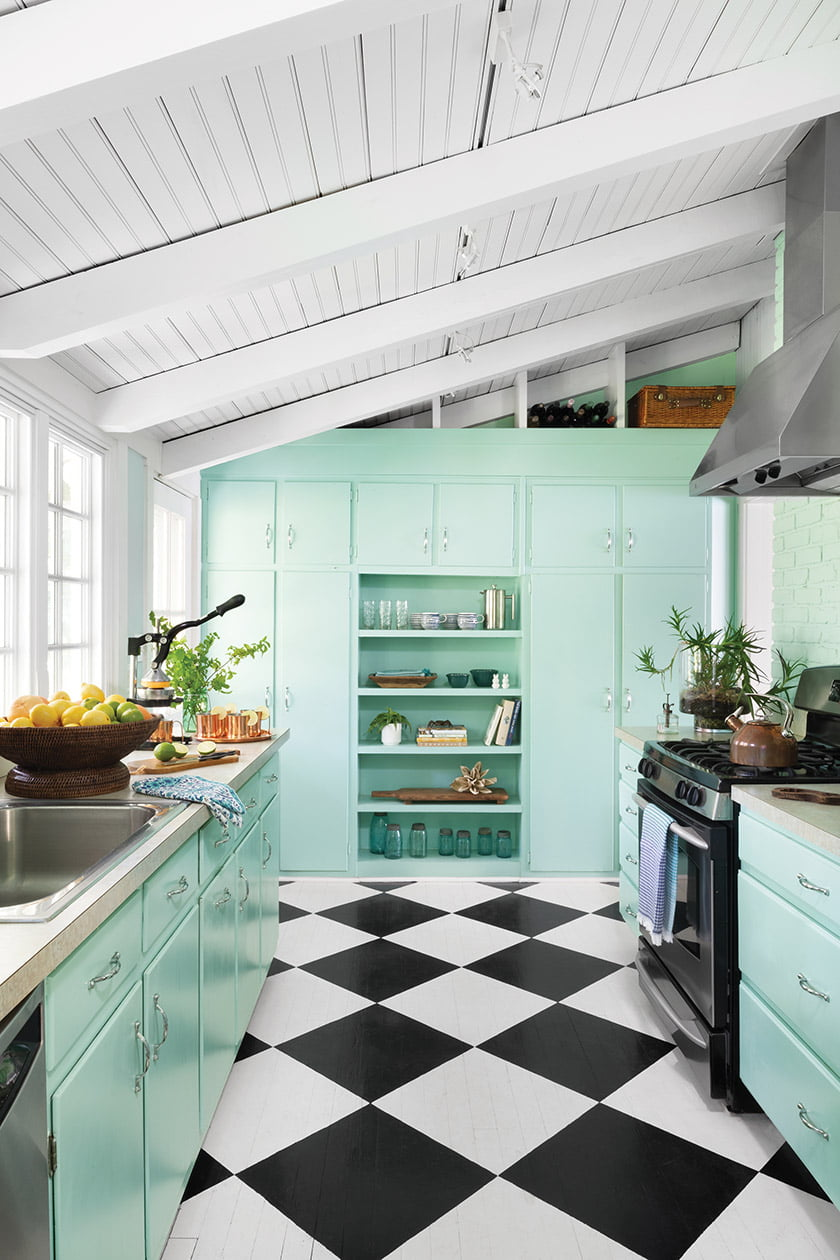 The designers revived old kitchen cabinets with a coat of Benjamin Moore's  Hannity Green; wood flooring painted in a harlequin pattern packs a punch.