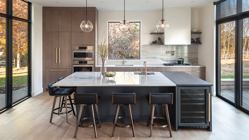 An island hosts casual meals in the kitchen; the countertops and backsplash are Mykonos quartzite. Photo: Daniel Grehl