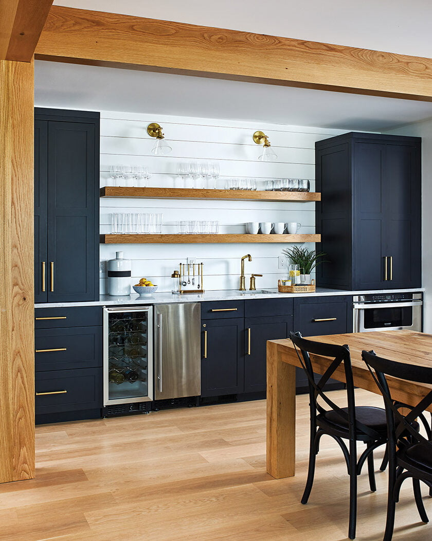 Shiplap siding and open oak shelving add airiness to a wall of cabinetry that houses a wet bar.
