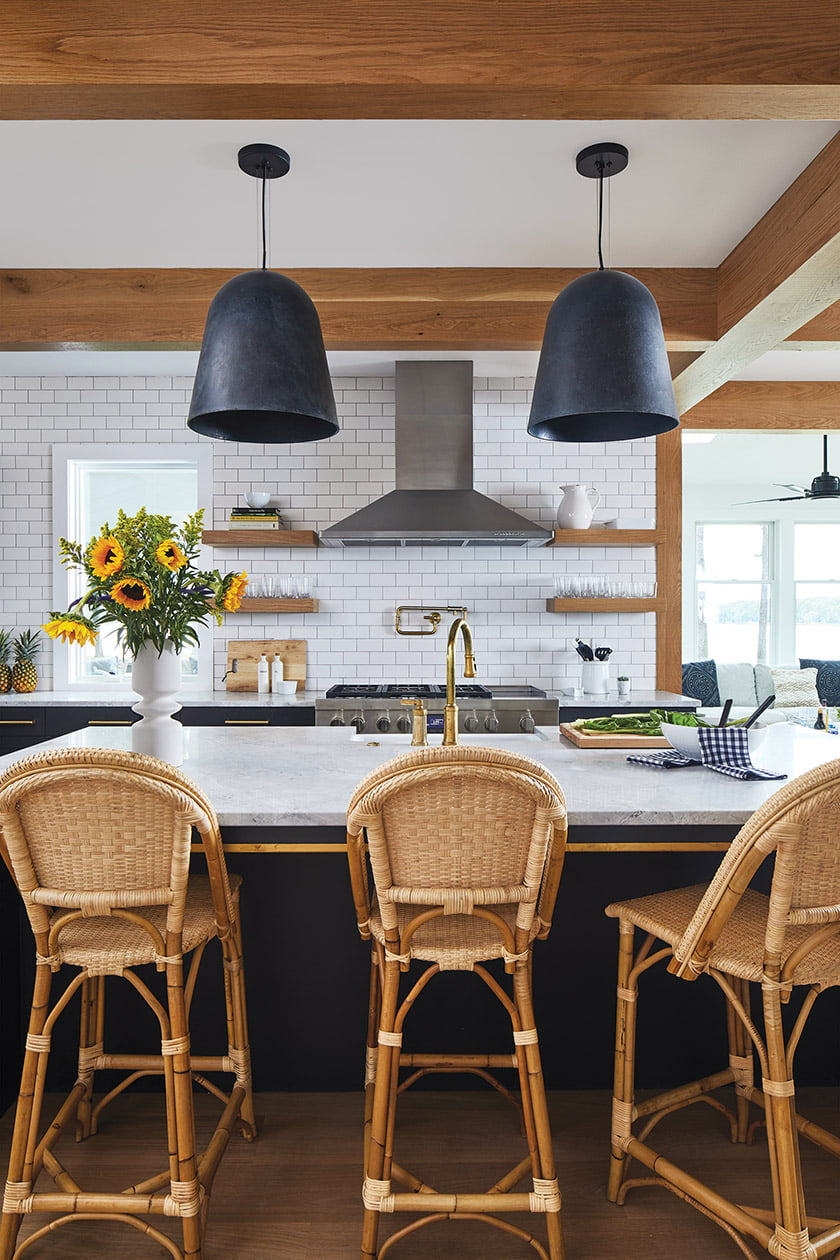 In the completed kitchen, white oak accents and woven Serena & Lily stools warm the graphic palette.