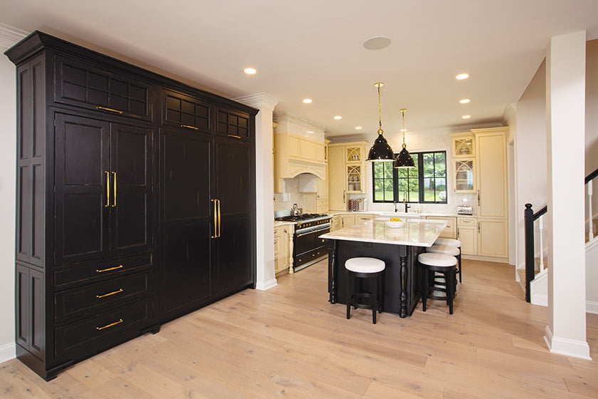 The kitchen's facelift included a new island, black-painted refrigerator and freezer panels, lighting and counter stools.
