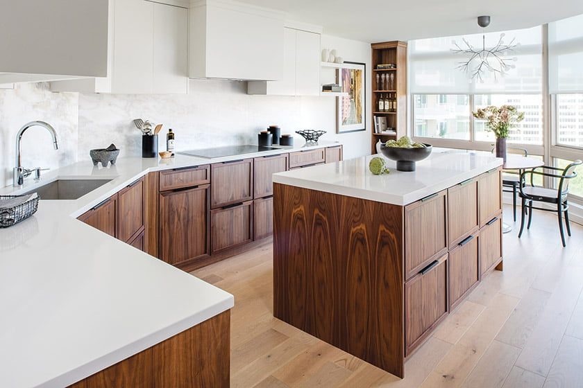 Meyer redesigned the kitchen with custom walnut base cabinetry and white upper cabinets to make the ceiling appear higher.