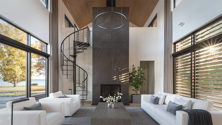 A fireplace clad in Porcelanosa tile creates a focal point in the double-height living room. A sliding panel of cedar slats allows residents to control daylight in the space, which enjoys cross-breezes when windows and doors are open.. Photo: Daniel Grehl