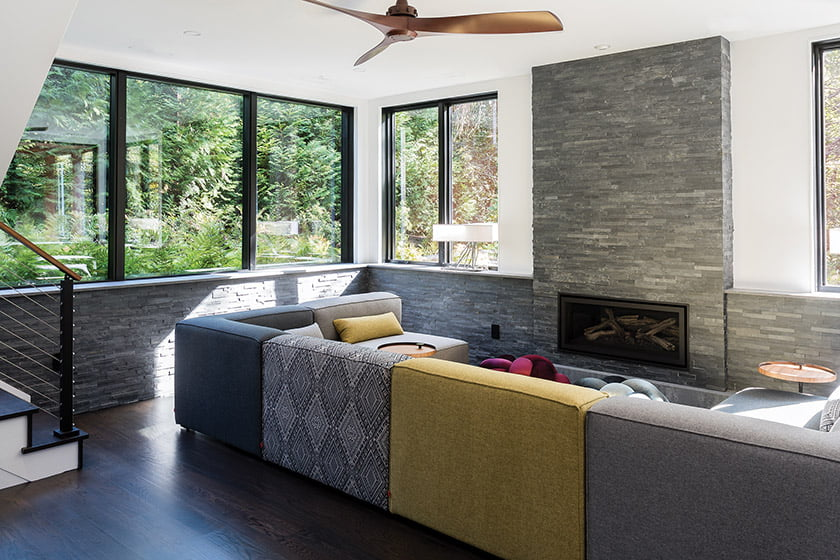 A lower-level space for lounging is anchored by a ledgerstone fireplace.