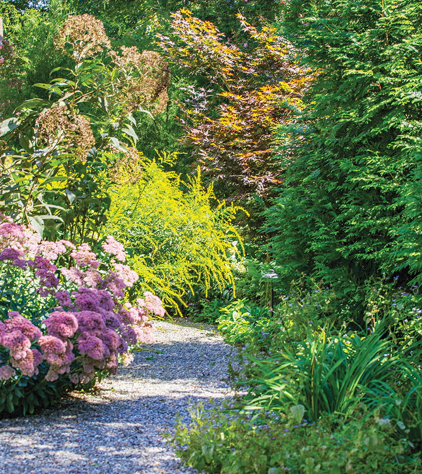 A natural path planted with perennials borders the south side of the property.