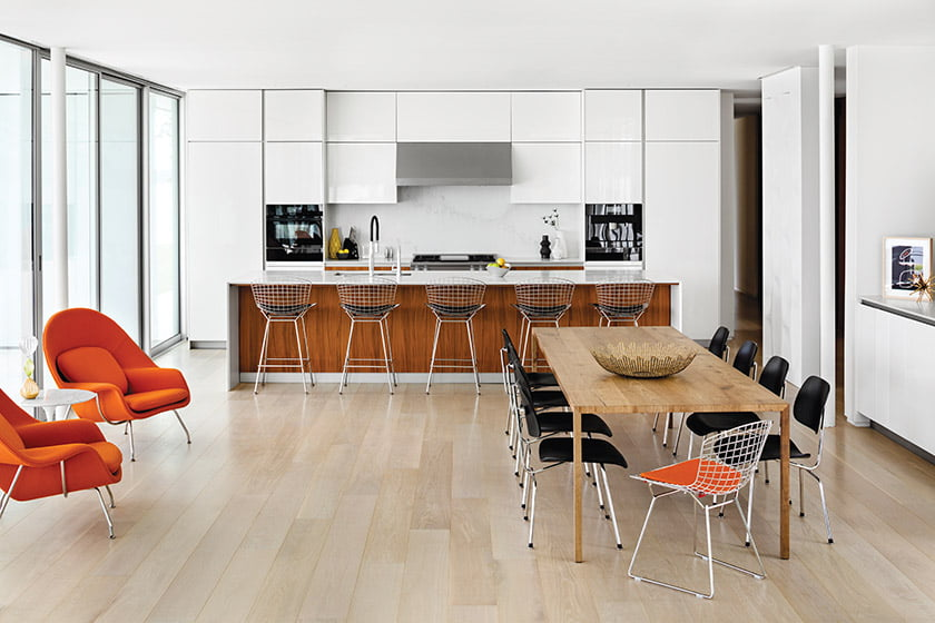 The open kitchen features white-lacquer and walnut cabinetry from Snaidero.