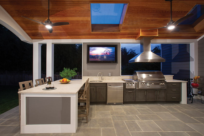 Outdoor kitchen with resin cabinets by NatureKast, quartz counters and a TV