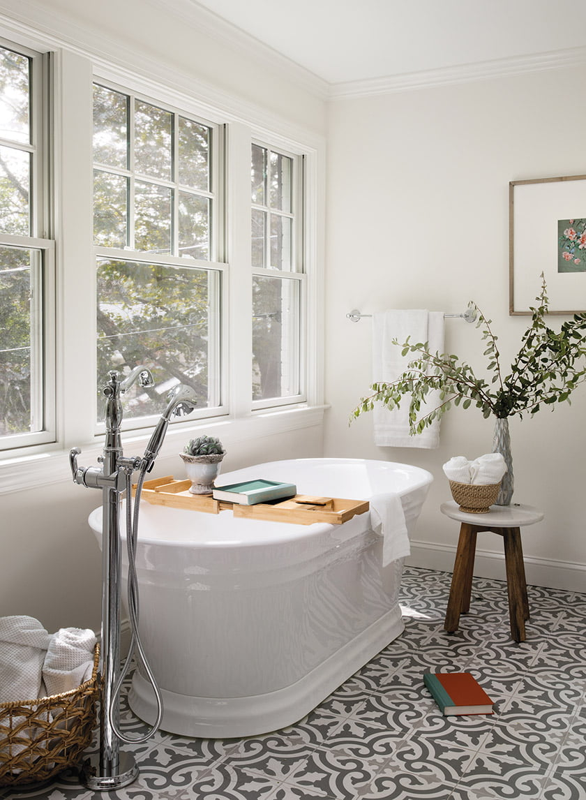 Patterned encaustic tile and a sculptural soaking tub add interest to the owners' bath.