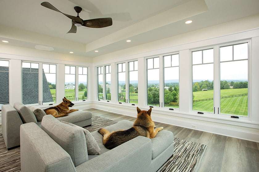 A new window-lined sunroom is a private retreat for watching the sunset—German shepherds in tow.