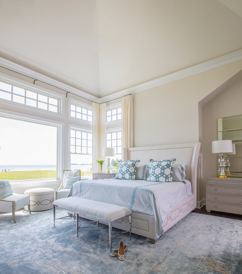 A custom rug by Erin Paige Pitts grounds the serene bedroom.