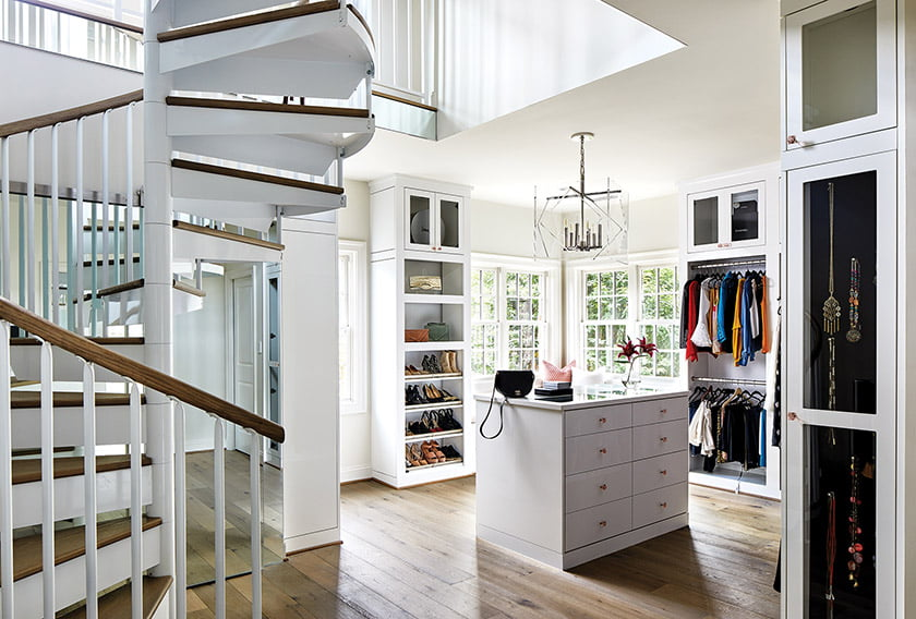 The owners' closet was designed by Tailored Living; a spiral stair leads up to a loft space carved out from the attic for additional storage.