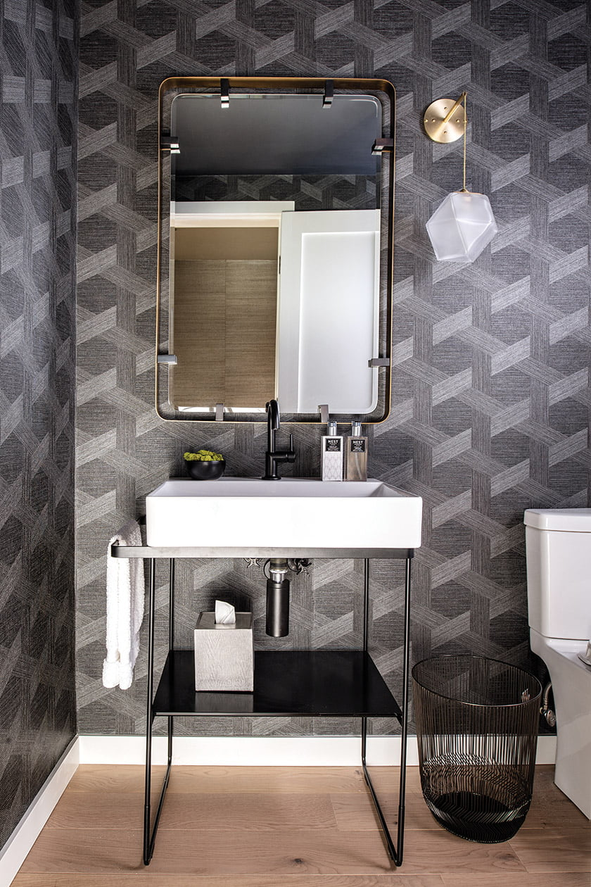 A moody vibe prevails in the powder room thanks to shimmery Philipp Jeffries wallpaper.