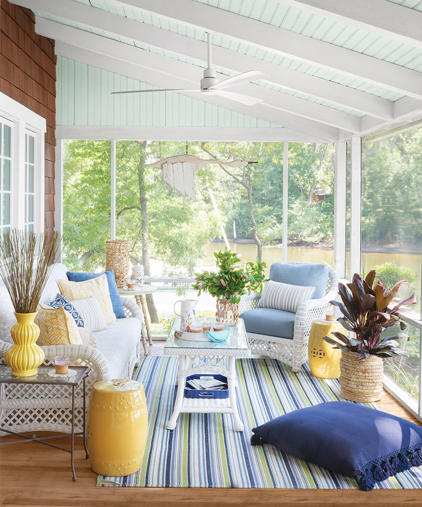 Pops of yellow make the screened porch a happy spot. The rug is by Dash & Albert and the wicker furniture is from Lane Venture.