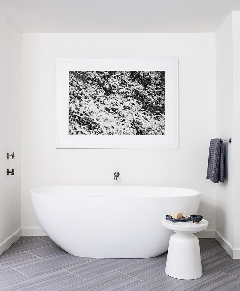 A photograph by the husband hangs above a sculptural tub.
