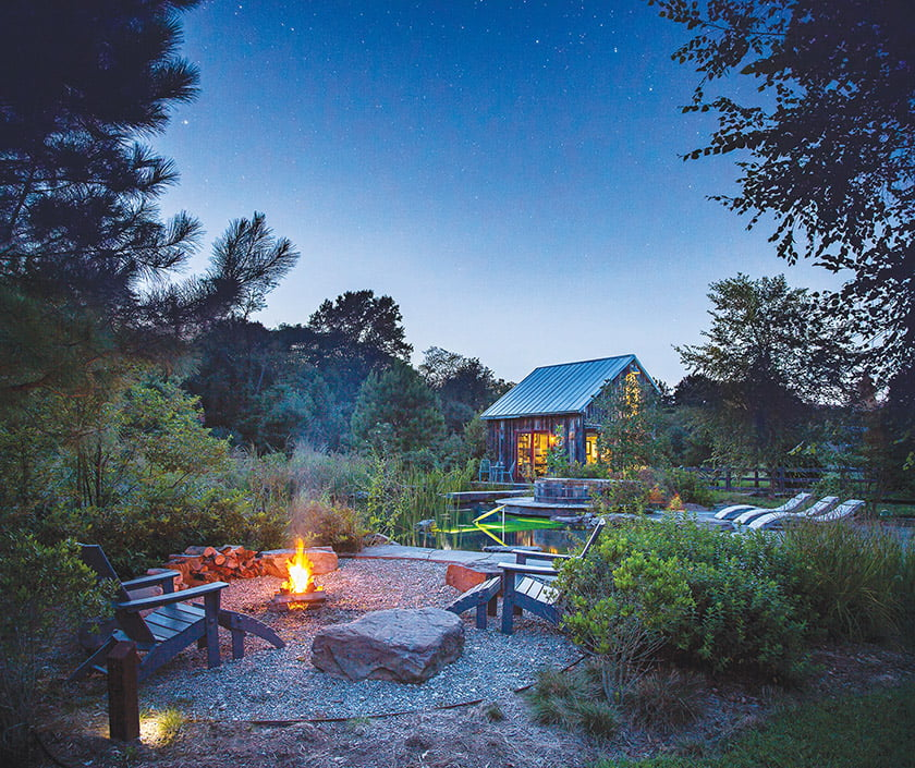 At twilight, a fire pit beckons under a starry sky.