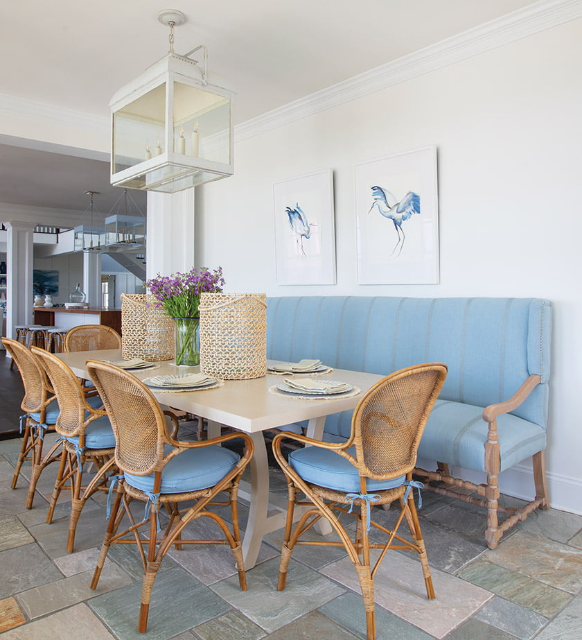 Delineated by slate flooring, the adjacent sunroom offers another mealtime option.