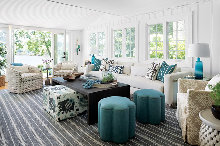The living room's custom Vanguard sofa is covered in indoor-outdoor Scalamandré fabric, while the ottoman is upholstered in Schlegel's favorite textile: Kravet's Inigo in the Agua/Verde colorway.