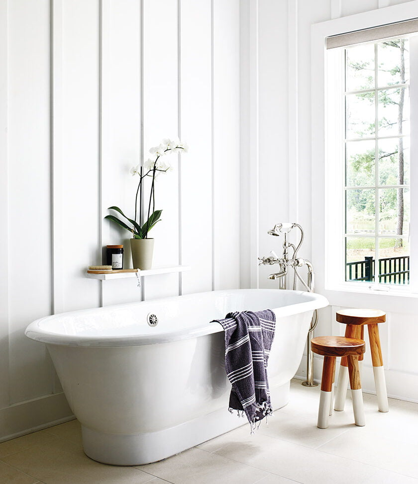 A Waterworks soaking tub conjures a vintage vibe against a wall clad in board-and-batten panels in the main-floor owners' bath.
