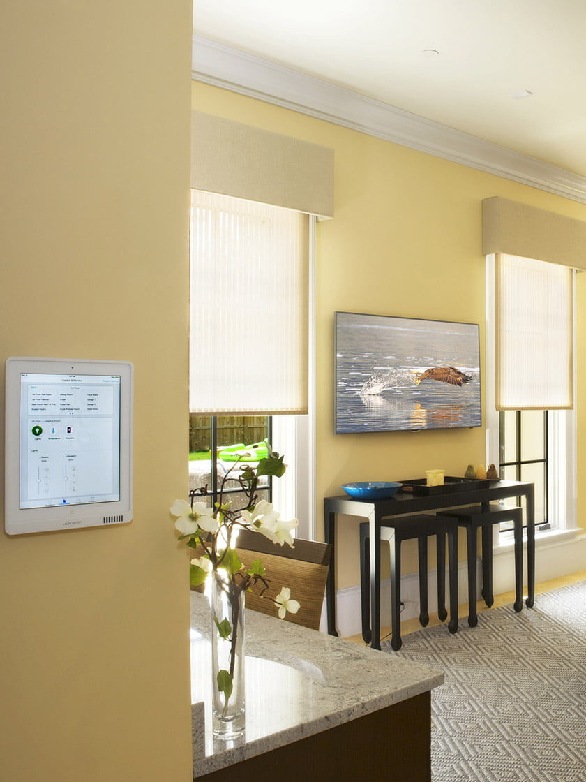 Motorized window treatments, an automated lighting system, whole-house audio and video entertainment are all controlled from an on-wall iPad.