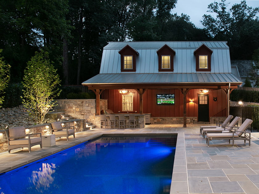 A backyard patio boasts the latest in outdoor technology: in-pool color-changing lights; a weather-proof TV; landscape audio; hardscape LED light fixtures; and a remote-controlled gas fire pit.