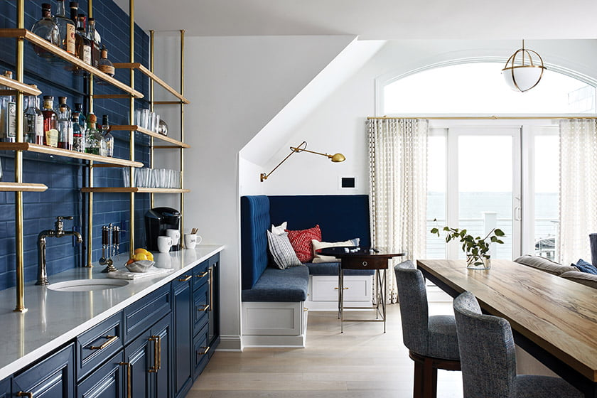 A clean-lined, second-level family room boasts a built-in wet bar surrounded by custom brass-and-glass shelving and a stylish, functional corner banquette.