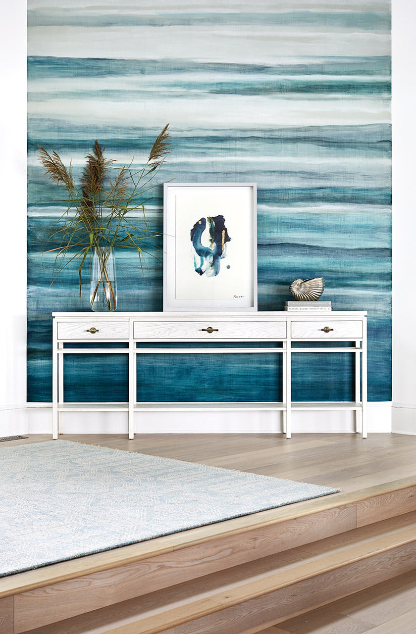 A custom, 19-foot-tall mural by Dee Lenehan conjures the sea in the foyer of an Ocean City getaway.
