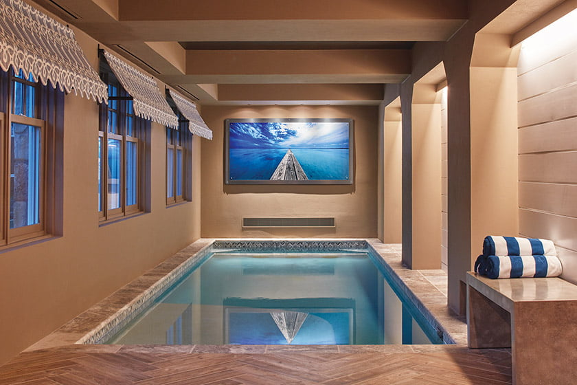 The lower level features an indoor pool transformed by porcelain-tile flooring  and a plaster wall finish.