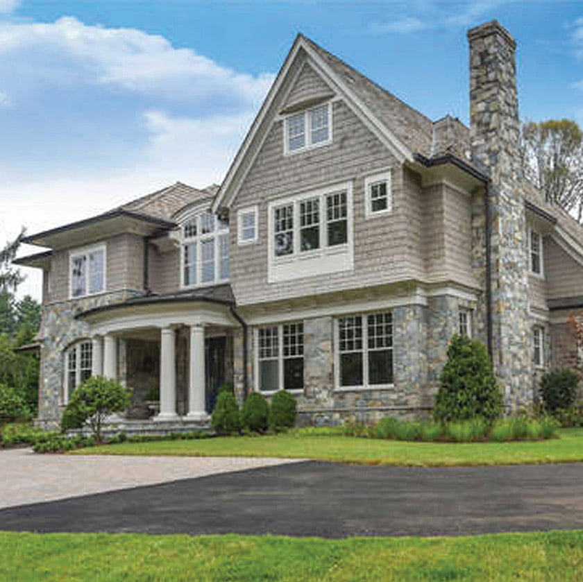 A warm mix of materials, from cedar shakes to stone, imparts interest and warmth to a traditional custom home in Spring Hill.