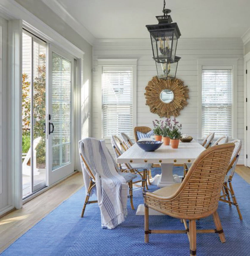 The dining room of a beach house channels its seaside locale via shiplap walls and a natural-wood sunburst mirror; a custom dining table is paired with woven chairs.