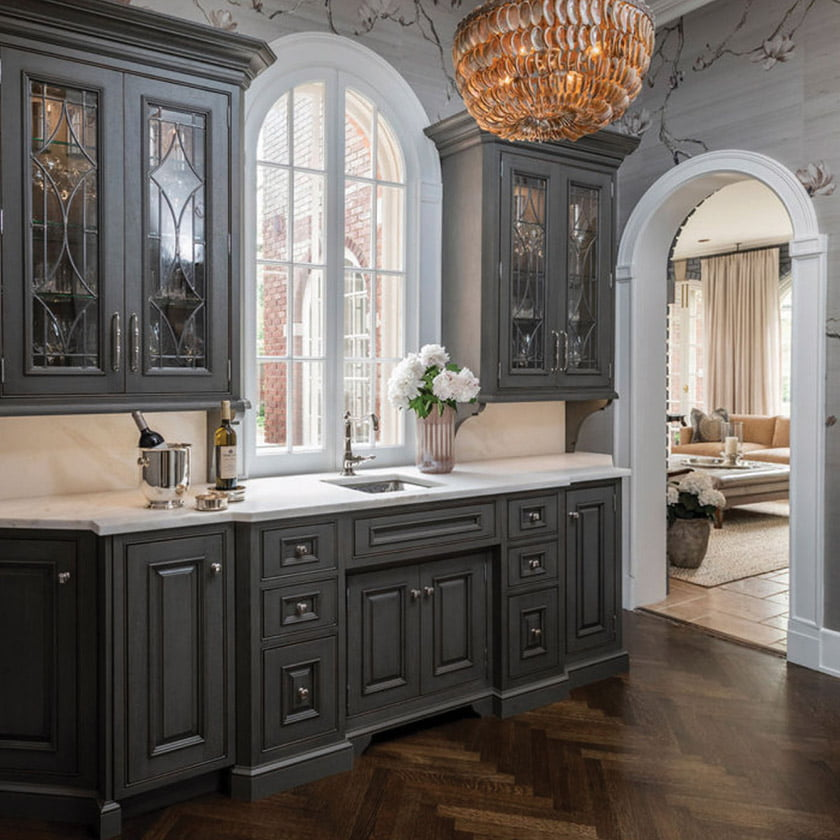 A traditionally styled wet bar beckons, with cabinetry custom fitted to frame an elegant arched window.